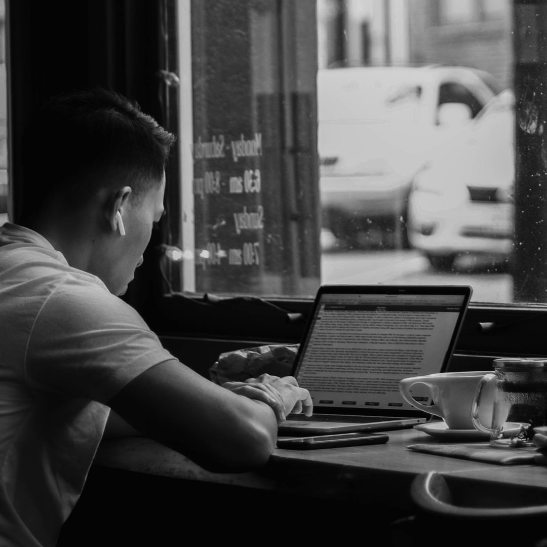 man sitting in cafe on laptop